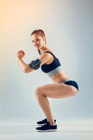 Side view on a cheerful brunette sportswoman looking into the camera with a smile on her face while warming up and squatting. Stock Photo