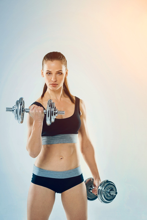 Serious young sportswoman with a ponytail looking into the camera while exercising with dumbbells and pumping up muscles.