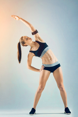 Full length shot of a beautiful fit female athlete focusing on a warming up exercise while standing on feet shoulder width and side bending.
