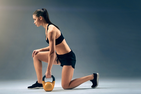 Side view on a motivated female athlete standing on one knee while doing weight exercises and lifting a heavy kettle-bell. Stock Photo