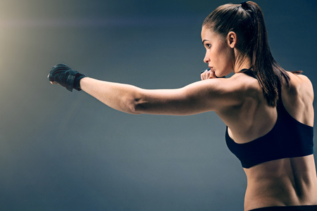 Side view on a confident female athlete wearing professional wrist wraps focusing her attention on an intensive training while boxing.