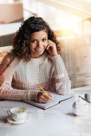 Cute positive young author sitting at the table in a beautiful cafe and smiling cheerfully while working at her first book