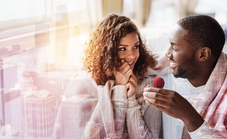 Close up of young pleasant couple sitting close to each other while holding a heart shaped box with wedding ring and expressing happiness Stock Photo