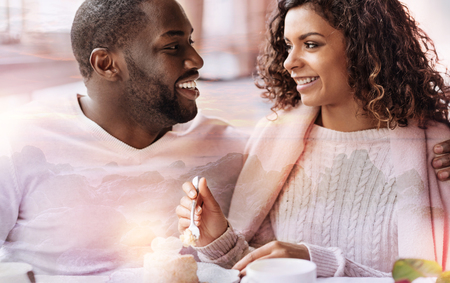 Close up of young smiling couple sitting in the cafe while looking at each in the eyes and showing true feelings Stock Photo