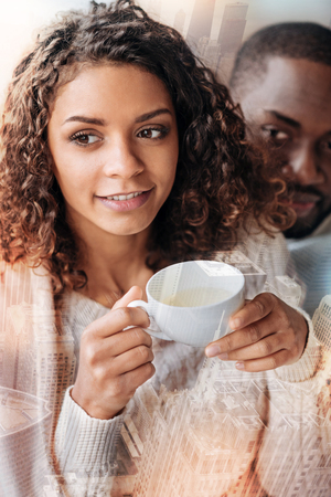 Close up of young pretty girl holding a cup of tea in hand while sitting with her boyfriend and looking away