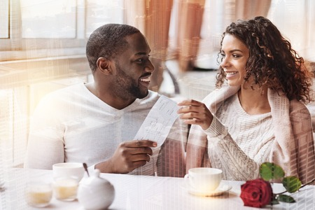 Positive man presenting flight tickets to his girlfriend while looking at her with love and expressing cheerful emotions Stock Photo