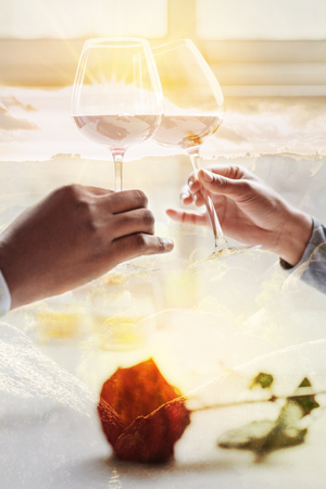 Close up of young pleasant couple holding glasses with wine and clanging while sitting in the cafe and enjoying being with each other Stock Photo