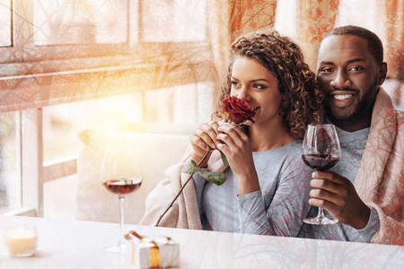 Close up of young cheerful couple sitting together while drinking wine and expressing happiness