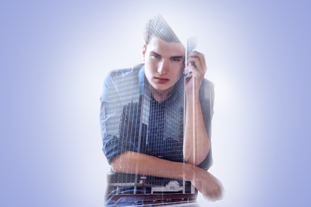 Pleasant handsome young man leaning on the chair and looking at you while living in a big city Stock Photo