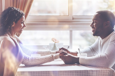 Smiling black man sitting in semi position opposite his girlfriend holding hands while being in cafe Foto de archivo