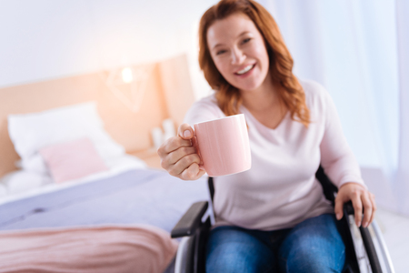 Pretty blond disabled woman of middle age smiling and suggesting some tea while sitting in the wheelchair and a bed in the background