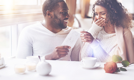 Our vacation. Smiling bearded black man turning his head to girlfriend while looking at her sitting together in the restaurant Stock Photo