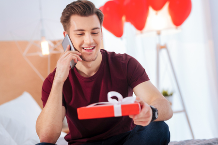 I am waiting for you. Radiant gentleman grinning broadly while looking at a present box and having pleasant phone conversation with his girlfriend. Reklamní fotografie