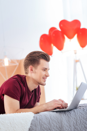Harmonious relations. Side view on a smiling guy lying on his bed and looking at a screen of his computer while chatting with his girlfriend online. Stock Photo