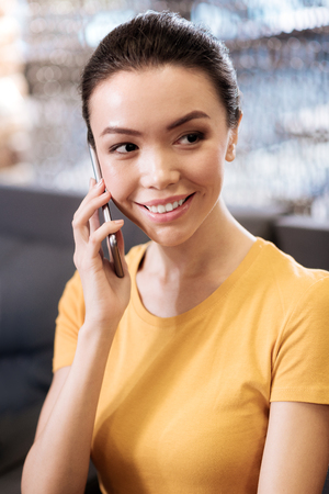 Attractive happy dark-eyed girl smiling and having hair tied up while talking on the phone