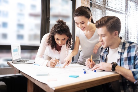 Draftsmanship. Good-looking happy concentrated aspiring young man and two ladies smiling while making a technical drawing and a girl holding compasses and a man holding a pencil