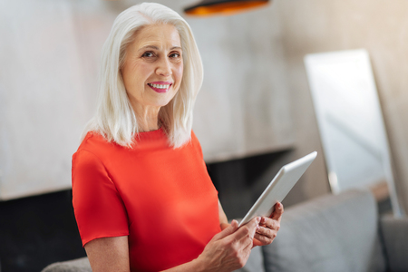 Happy positive elderly woman sitting at home and smiling while using a tablet Imagens