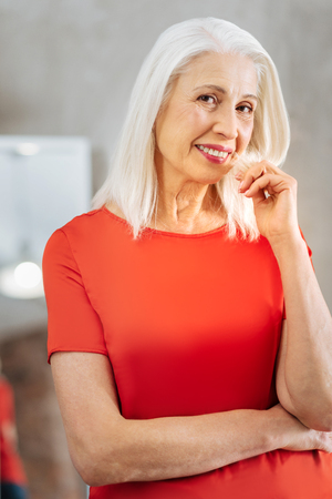 Nice pleasant cheerful elderly woman holding her hair and smiling while looking at you