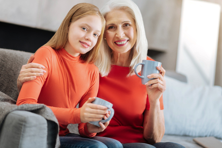 Nice delighted aged woman hugging her granddaughter and smiling while enjoying tea together with her