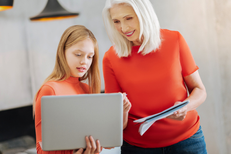 School project. Nice smart pleasant girl holding a laptop and talking to her grandmother while preparing a school project