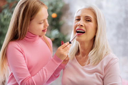 Positive cute nice girl holding a lipstick brush and applying it on the lips while putting makeup on her grandmother