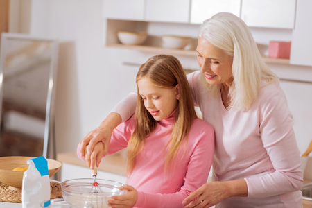 Joyful pleasant senior woman holding a whisk and smiling while teaching her granddaughter to whip