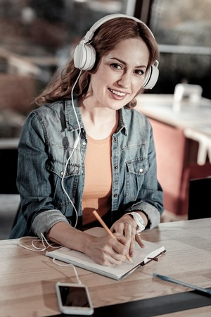 Nice music. Smart cheerful beautiful woman sitting in a cafe and listening to music in big headphones and making notes in her notebook