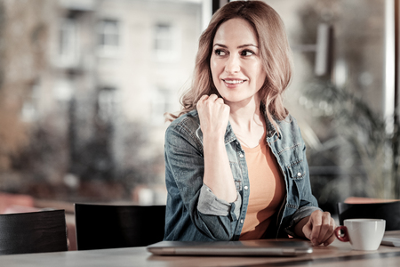 Attentive glance. Pleasant beautiful young woman sitting in a cafe and looking to the right side while drinking her coffee and waiting for a friend