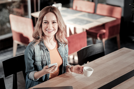 Happy visitor. Cheerful positive young woman sitting in a cafe and drinking coffee while holding a modern smart phone and smiling Stock Photo