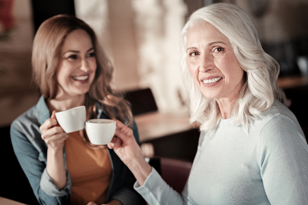 Cheerful women. Beautiful positive elderly woman looking glad while drinking coffee and having a good time with her granddaughter