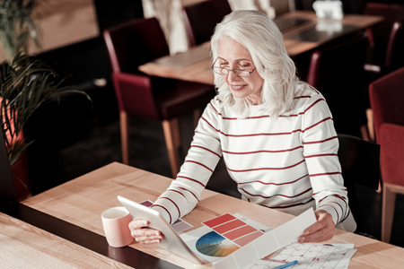 Exciting work. Smart enthusiastic elderly designer looking cheerful and attentive while sitting at the table and working with different bright color palettes