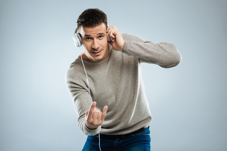 Hard rock. Attractive man wrinkling forehead and touching headphones while looking straight at camera