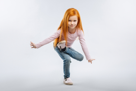 Making trick. Pretty kid expressing positivity and maintaining the balance of power while standing over grey background