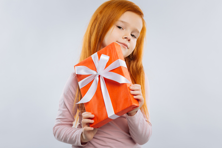 It is mine. Delighted kid pressing lips and holding box while looking straight at camera Stock Photo