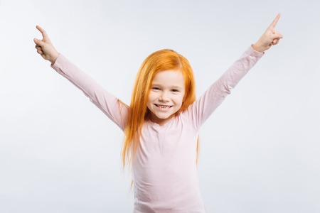 I am pleased. Smiling kid keeping smile on her face and holding hands up while looking straight