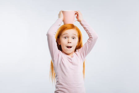 Being frolic. Amazing red-haired girl opening mouth and raising eyebrows while looking straight at camera