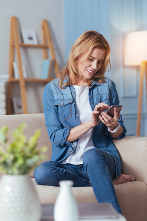 Typing messages. Cheerful beautiful young woman feeling interested while sitting on a comfortable sofa and typing a message on her modern convenient smartphone