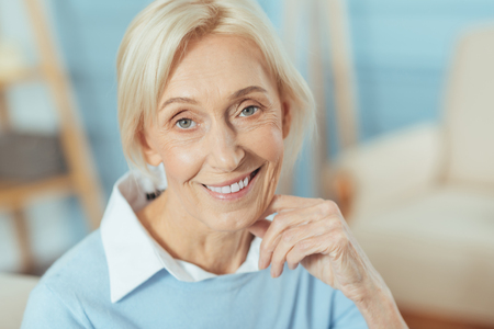 Lovely afternoon. Cheerful pleasant senior woman looking happy while sitting with her hand near the face and smiling kindly when waiting for her daughter Stock Photo