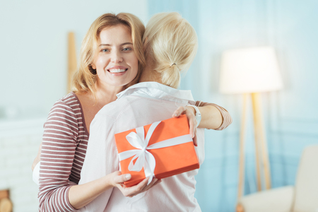 Memorable day. Cute beautiful attentive woman feeling happy while having a lovely present for an aged grandmother during her birthday Stock Photo