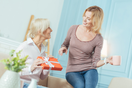 Surprise. Emotional senior woman feeling happy after getting a great present from her attentive kind young granddaughter Stock Photo