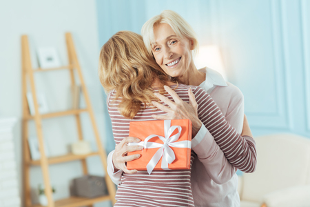 Excited grandmother. Cheerful emotional senior woman feeling happy while hugging her young relative after getting a wonderful present from her
