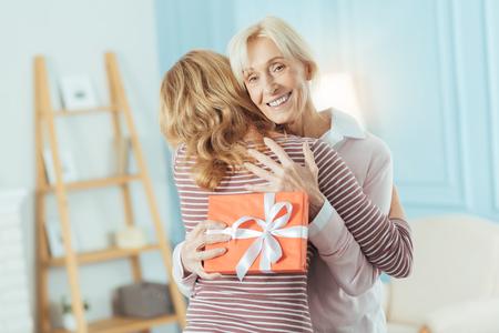 Opgewonden grootmoeder. Vrolijke emotionele senior vrouw voelt zich gelukkig terwijl ze haar jonge familielid knuffelt na het krijgen van een prachtig cadeau van haar