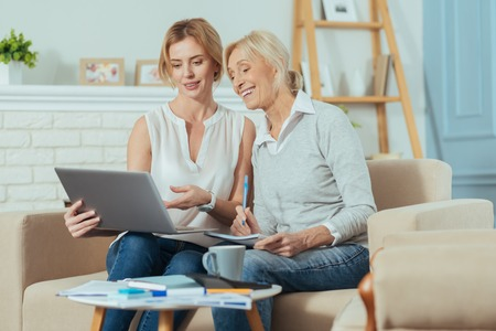 Good results. Responsible clever aged woman feeling happy while looking at the screen of a modern laptop and having an important conversation with her experienced reliable financial advisor