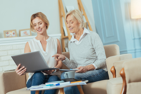 Not bad. Cheerful young financial advisor looking at the screen of her laptop while a happy senior woman sitting by her side with a little notebook and feeling good