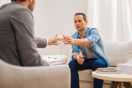 Calm is everything. Crying male patient desiring glass of water and sharing his problems while skillful psychologist holding water