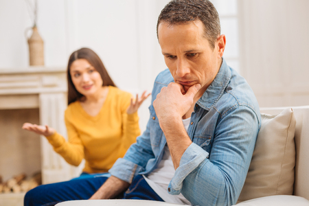 Domestic war. Crying upset woman asking for explanation while thoughtful man sitting and placing his hand under the chin