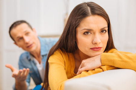 Important reason. Beautiful dreamful upset woman  looking in nowhere  while ignoring her husband and sitting Stock Photo