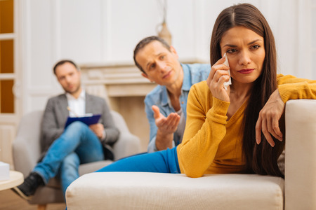 Your words hurt. Gentle offended song woman looking aside holding tissue  while husband talking to her Stock Photo