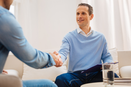 Pleasant  acquaintance. Attractive handsome kind man smiling sitting on the sofa and shaking hands