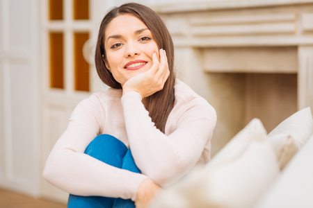 Warm atmosphere.  Pretty wonderful attractive woman smiling sitting and gazing at the camera Stock Photo